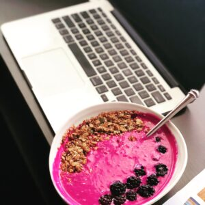 Quick healthy acai breakfast bowl while eating at the computer